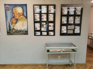 """Fragment wystawy """"W stulecie urodzin papieża Polaka"""" - gobelin przedstawiający Jana Pawła II, antyramy i gablota ze znaczkami."""