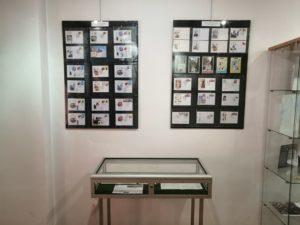 """Fragment wystawy """"W stulecie urodzin papieża Polaka"""" - antyramy i gablota ze znaczkami."""